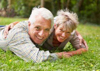 Glückliches Paar Senioren liegt lachend auf einer Wiese im Sommer