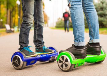 Feet of girl and boy riding electric mini segway outdoors in park. Ecological city transportation on battery power.