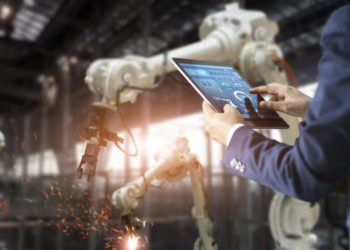 Manager industrial engineer using tablet check and control automation robot arms machine in intelligent factory industrial on real time monitoring system software. Welding roboticts and digital manufacturing operation. Industry 4.0 concept